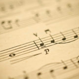 Classical music - notes on yellowed vintage paper sheet (shallow DOF)