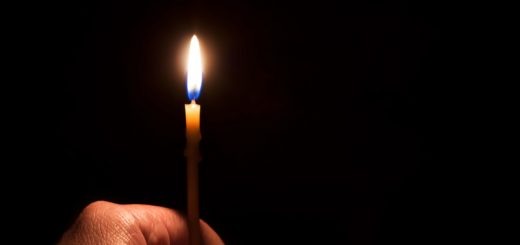 The hand holding a burning candle on a dark background